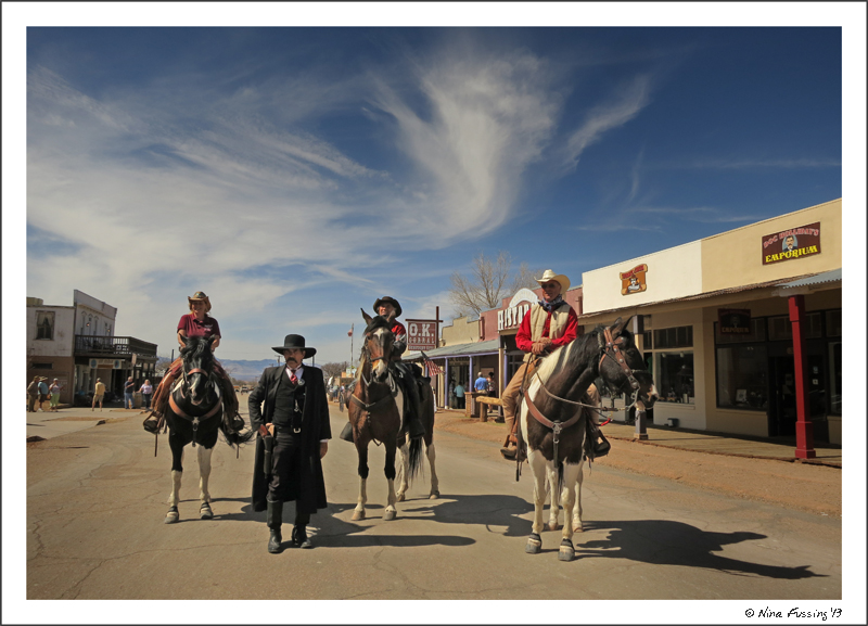 3 tourists on horseback pose with Wyatt Earp in downtown Tombstone