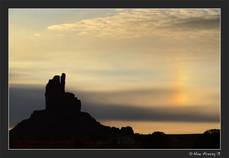 A faint rainbow at sunrise behind one of the Mittens