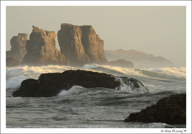 The low sun lights up waves by the sea stacks